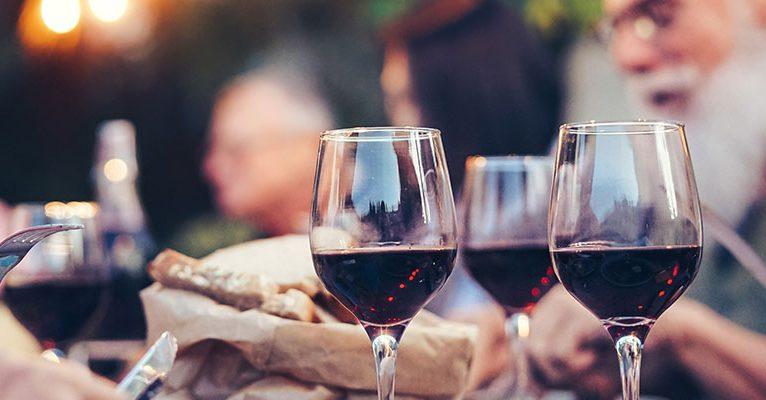 Fröhliches Familienessen und Rotwein trinken bei Dinner-Party