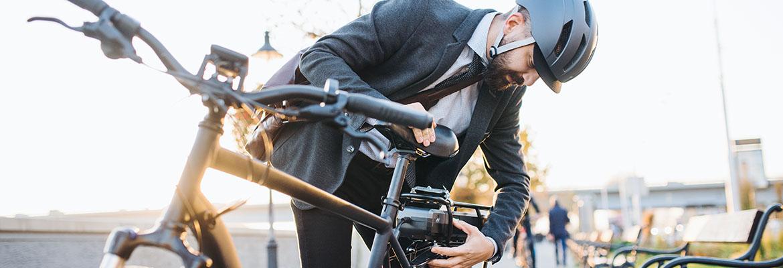 Geschaeftsmann faehrt mit dem Elektro-Fahrrad zur Arbeit