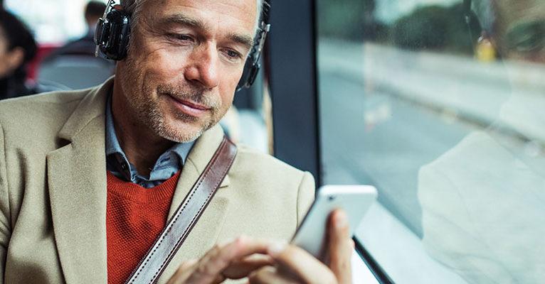Geschäftsmann mit Smartphone unterwegs im Bus