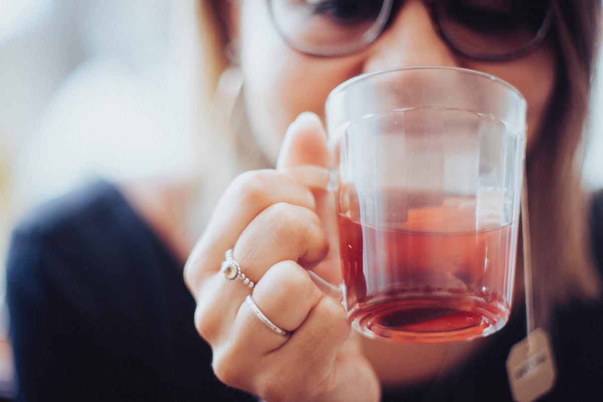 Frau trinkt aus einer Tasse Tee.