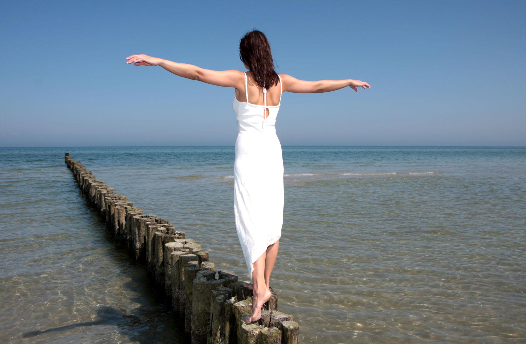Frau in weißem Kleid balanciert auf Holzbuhnen über Sandstrand ins Meer hinein