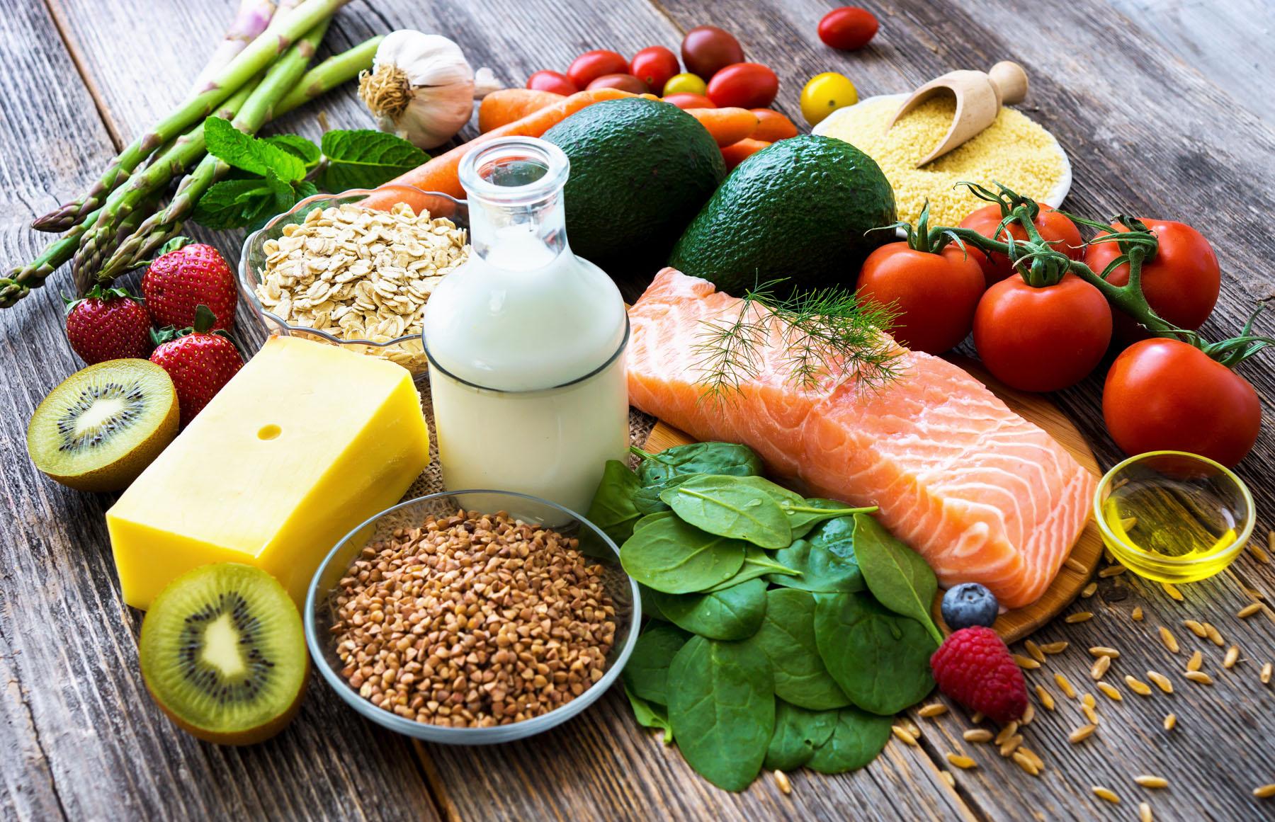 Verschiedene gesunde Lebensmittel auf einem Holztisch.