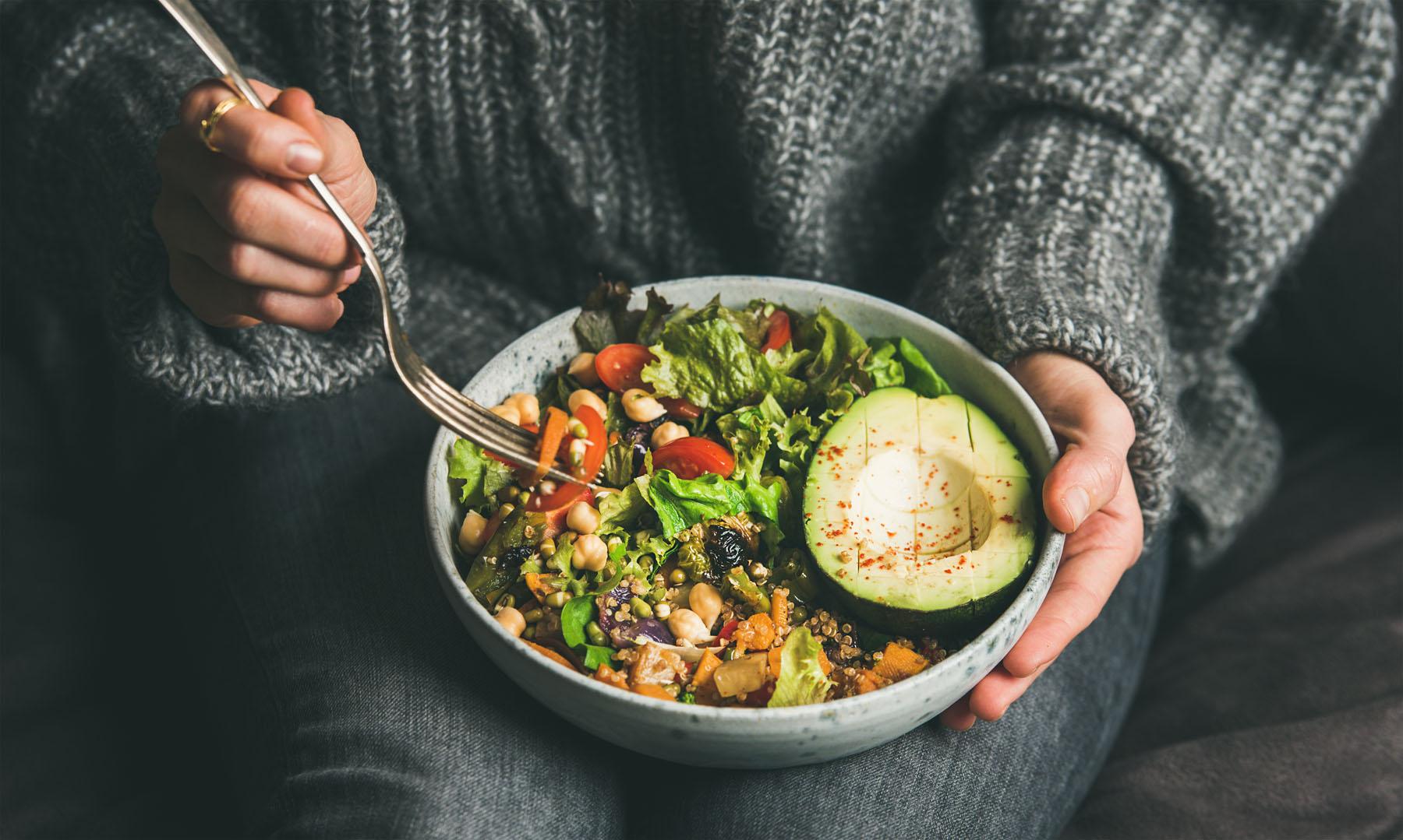 Eine Person hält eine Schüssel mit gesunden Lebensmitteln und eine Gabel.