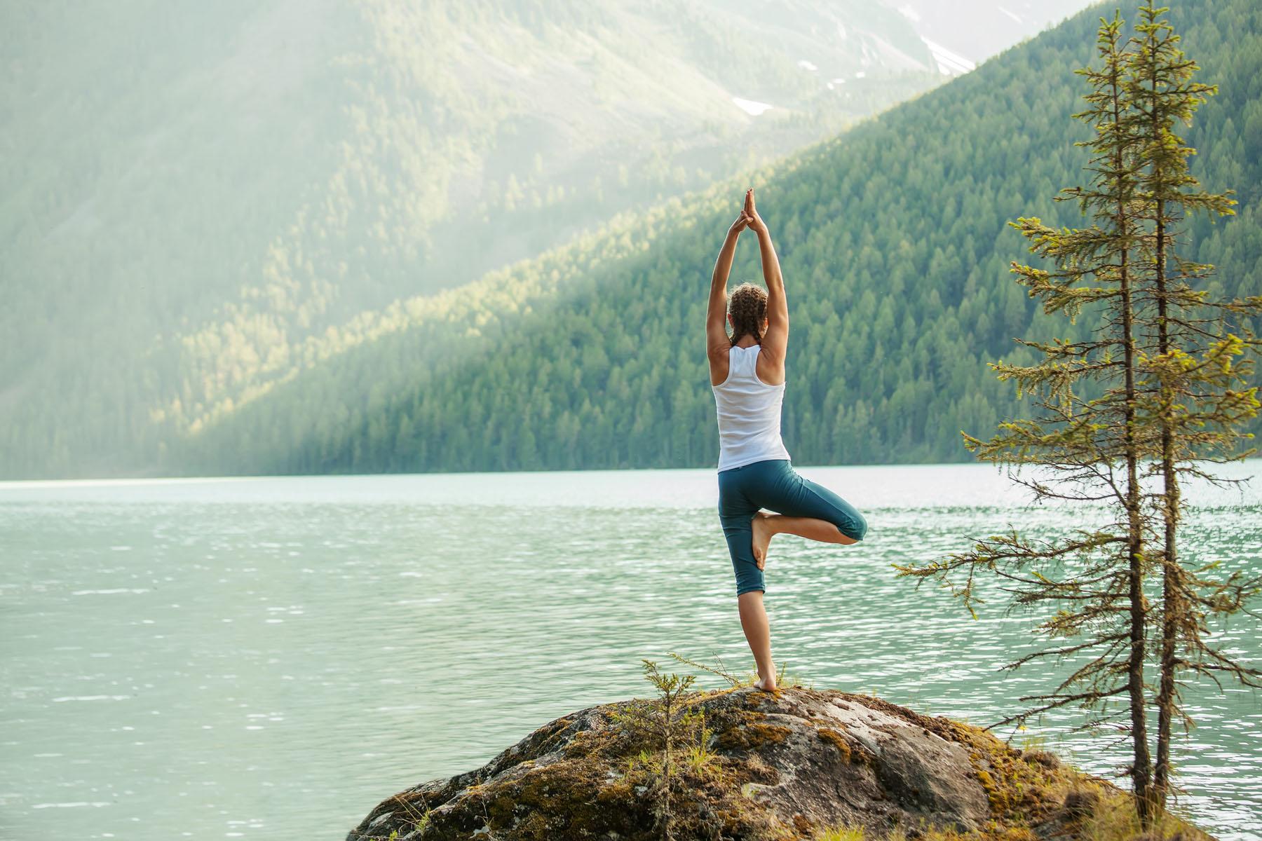 Frau balanciert einbeinig in Yogapose auf einem Felsen am Ufer eines Bergsees